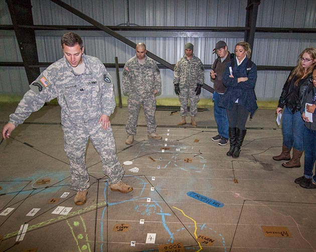 MISSION PREP--Capt. Dave Provencher, of the 1-24th Infantry command staff, walks News Writing students through a scale map of exercises involving his regiment and other units of Fort Wainwright's 1-25 Stryker Brigade.