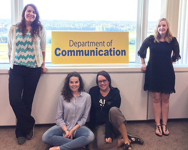 Communication Graduate Students pose for a quick photo on campus.